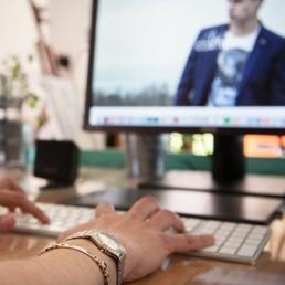 mano su tastiera e sullo sfondo il monitor