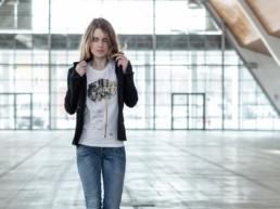 una donna passeggia indossando una t-shirt donna Paul Cortese sotto un giacchino nero