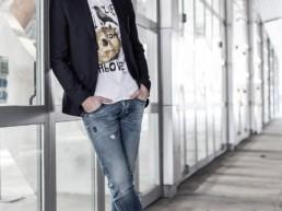 un uomo indossa una t-shirt Paul Cortese sotto una giacca nera