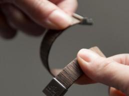 Due mani mostrano la flessibilità di un bracciale in legno Paul Cortese